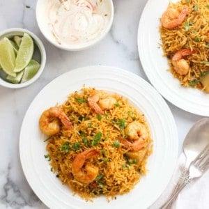 shrimp biryani with raita and lime wedges