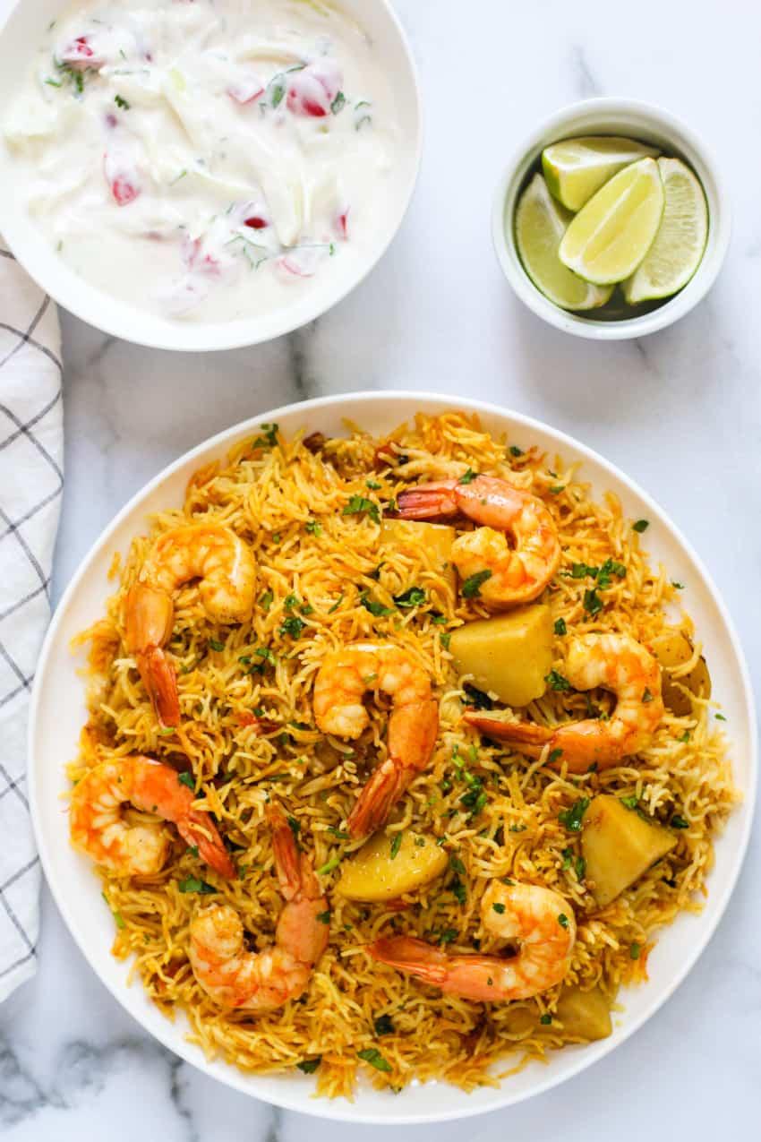 shrimp biryani served with raita and lime wedges