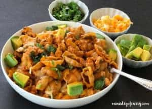 spicy taco pasta served in a white bowl, small bowls of cilantro, cheese and diced avocado on the side