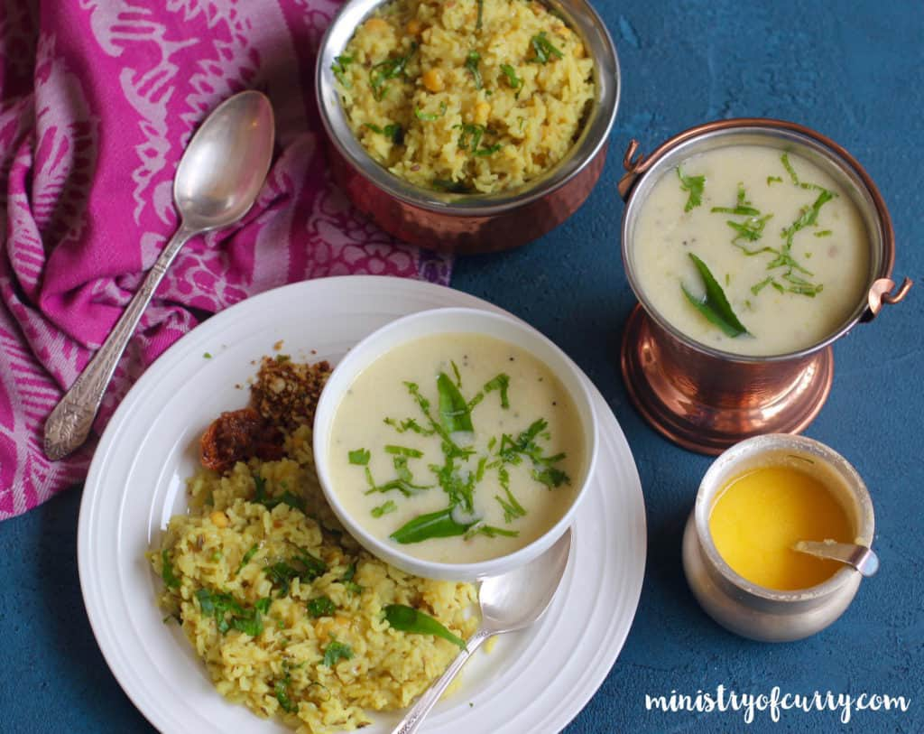 White dinner plate with khichdi and pickle served woth a bowl of kadi. Also a serving bowl of khichdi, kadhi and ghee on the outside