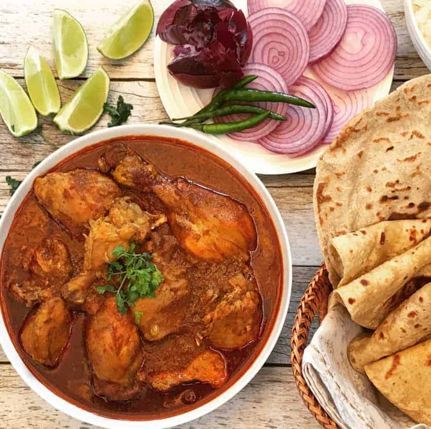 Chicken Curry in a bowl with rotis, lime wedges and sliced onions on the side