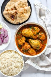 Chicken Curry in a white bowl with rice, chapatis and sliced onions on the side