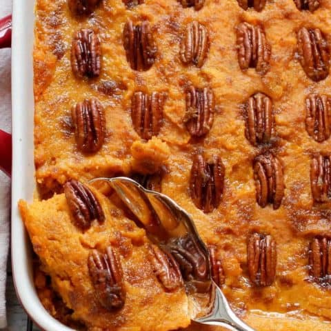 Sweet Potato Casserole in a served dish with a spoon scooping out some of it.