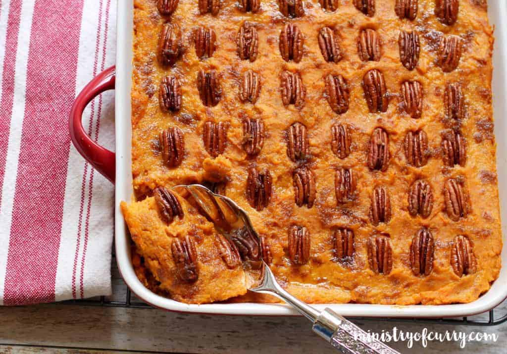 sweet potato casserole in a large serving dish with a serving spoon in it