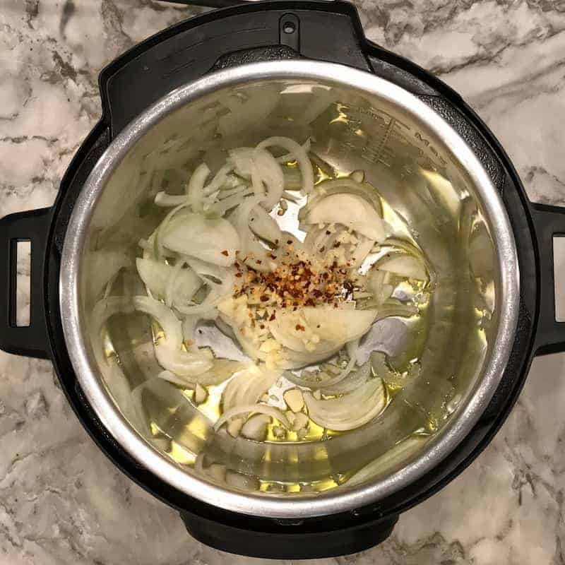 Instant Pot with oil, sliced onions, garlic and red chili pepper flakes