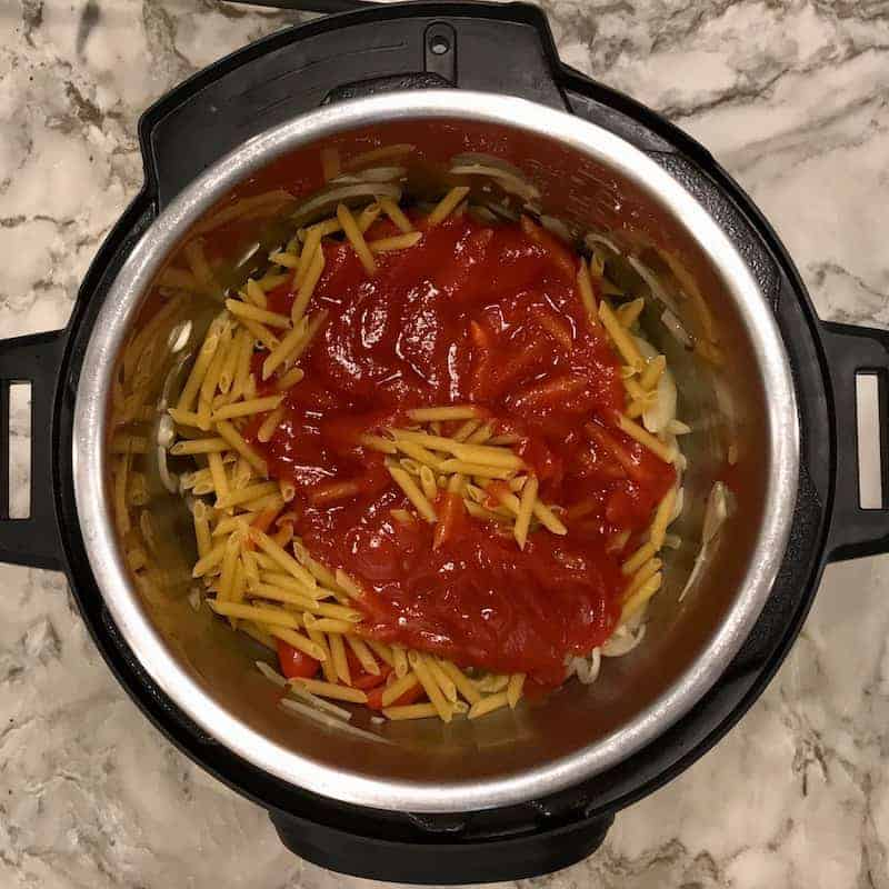 Instant Pot with dry pasta and tomato sauce layered over it.