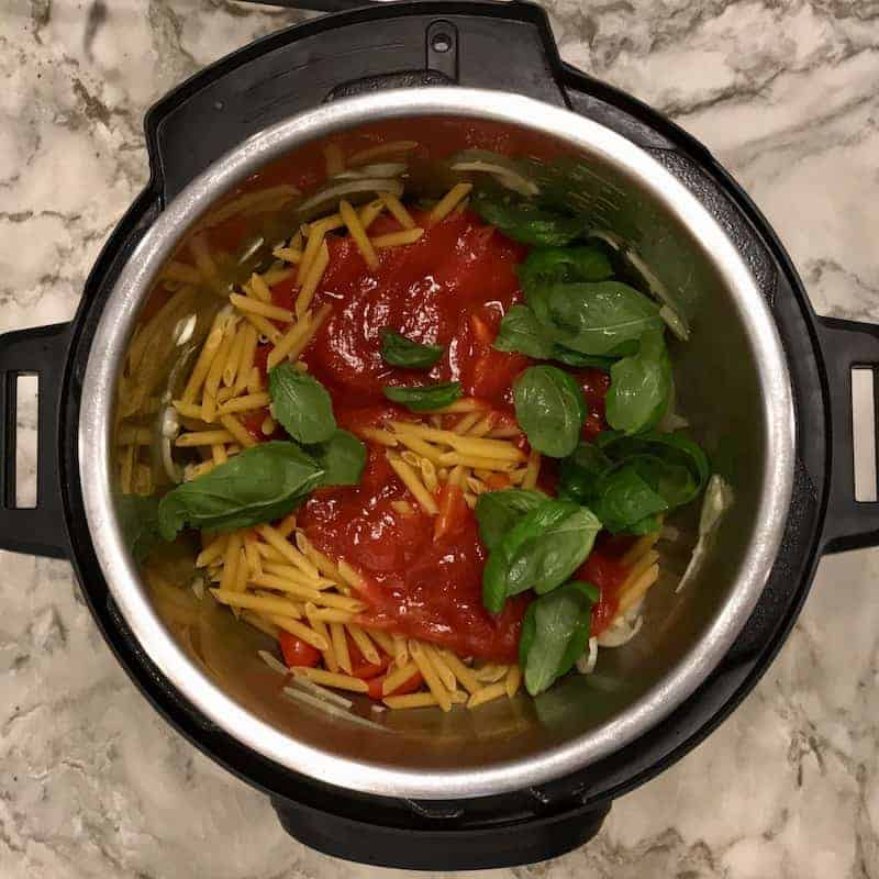 Instant Pot with dry pasta and tomato sauce and basil leaves layered over