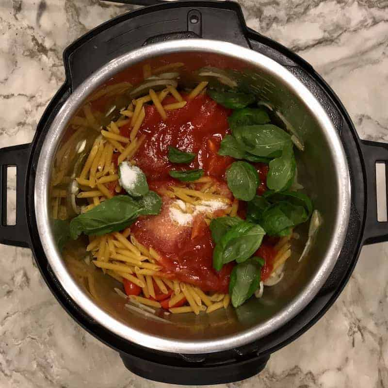 Instant Pot with dry pasta and tomato sauce, basil leaves and salt layered over