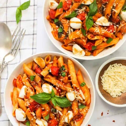 pasta caprese served in 2 white bowls