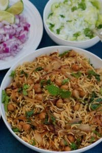 White Bowl with Chickpea Biryani. Two small white bowls on the side with cucumber raita and diced onions