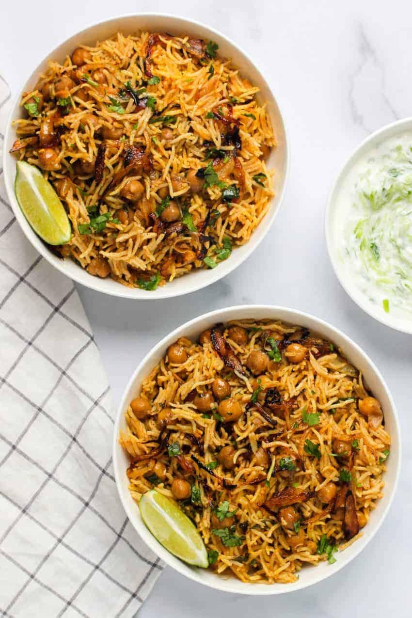 two bowls of chickpea biryani and raita on the side