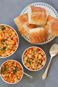 3 white bowls with Pasta e Fagioli soup and a platter of sliced baguette