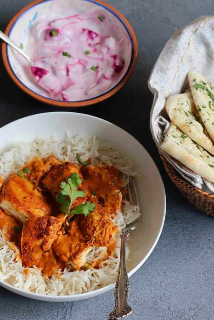 Chicken Tikka Masala serevd in a white bowl over white rice. Served with naan and raita alongside.