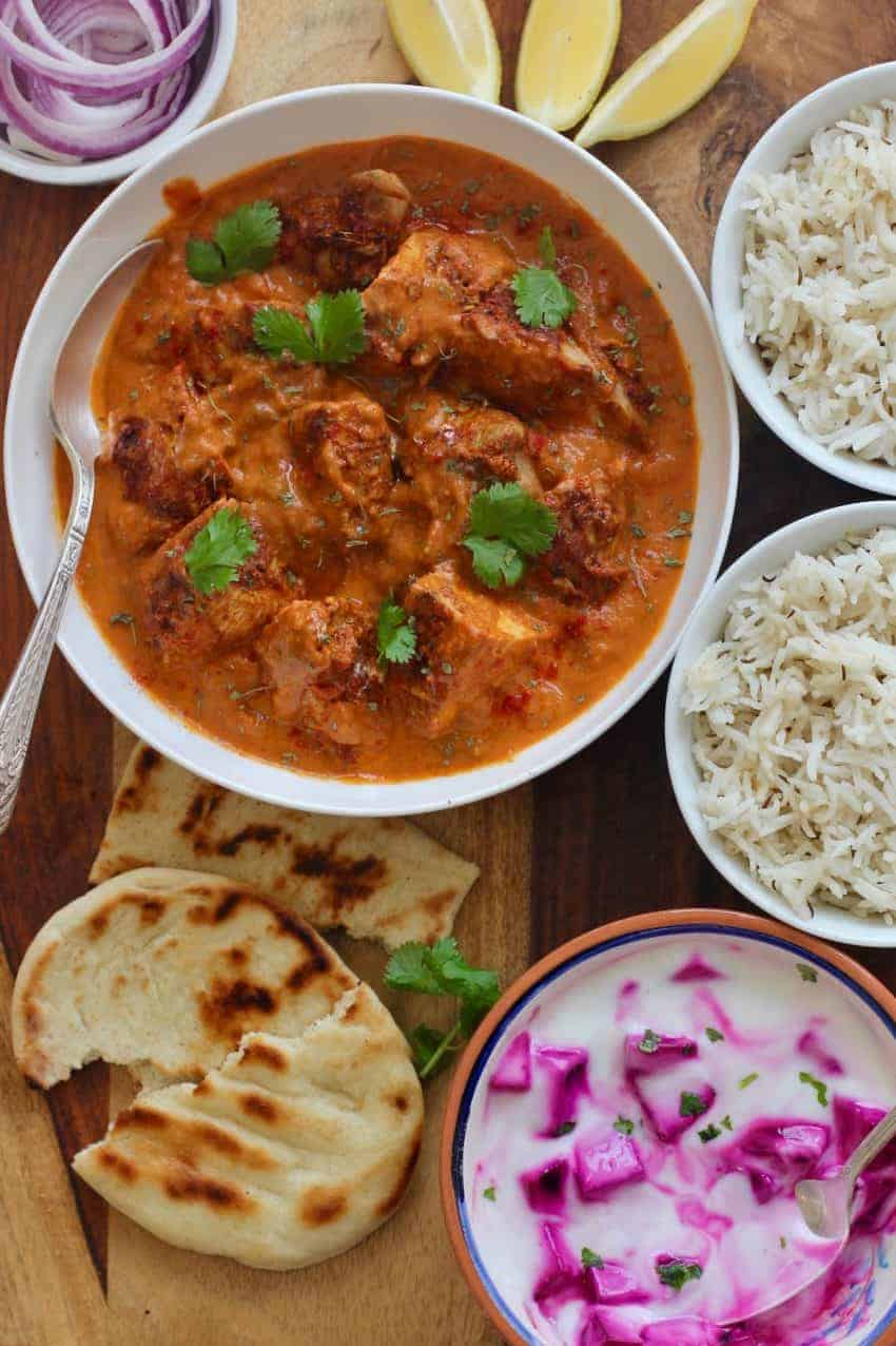 Chicken Tikka Masala in a white bowl, 2 bowls of rice, a bowl of beet raita and naan on a wooden board