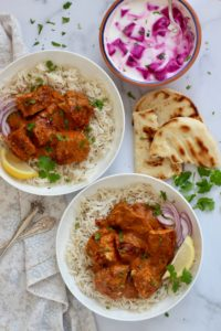 Chicken Tikka Masala served over white rice, garnished with cilantro and lemon wedge on the side. Naan and beetroot raita on the side.