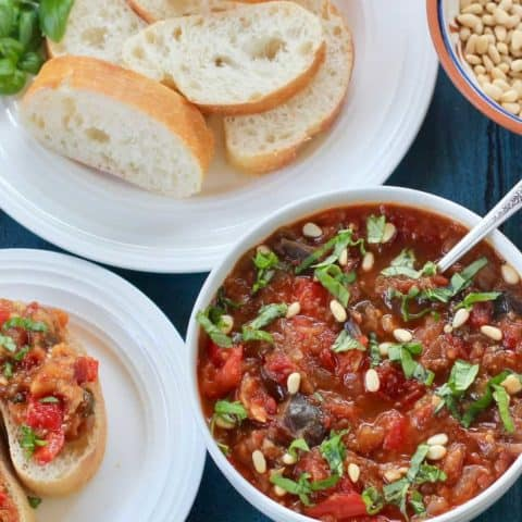 White Bowl with eggplant & red pepper spread, with sliced italian bread on the side in a white plate