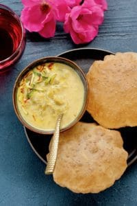 Dudhi Basundi in a bowl with puffed pooris served on the side