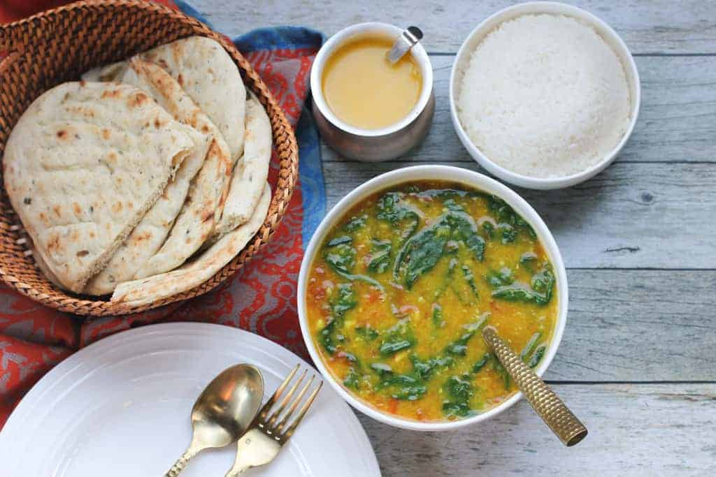 Spinach Dal in white bowl, bowl of white rice, and naan
