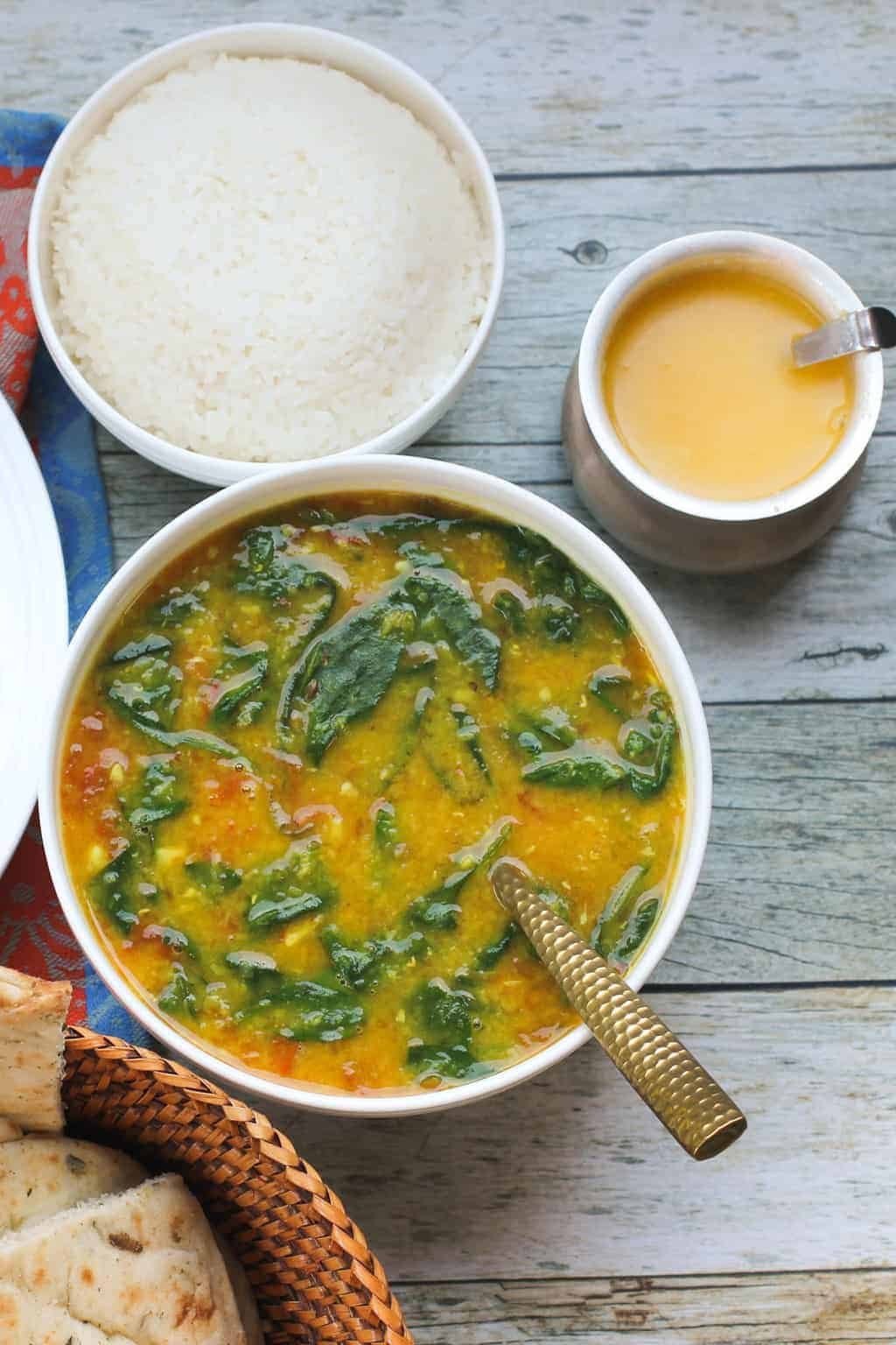 Spinach Dal in white bowl with bowl of rice