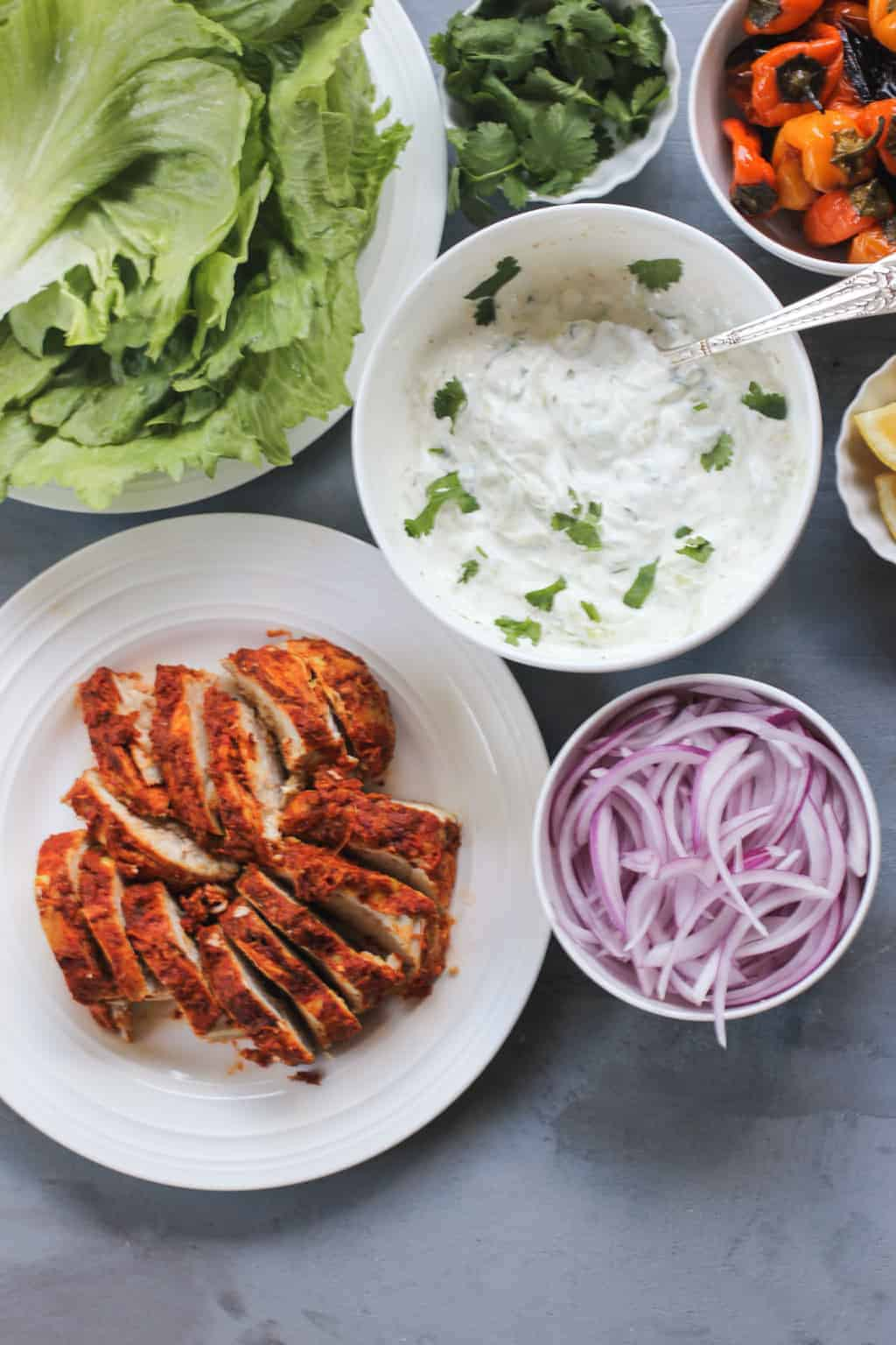 Tandoori Chicken sliced on white platter with bowl of red onion, and raita
