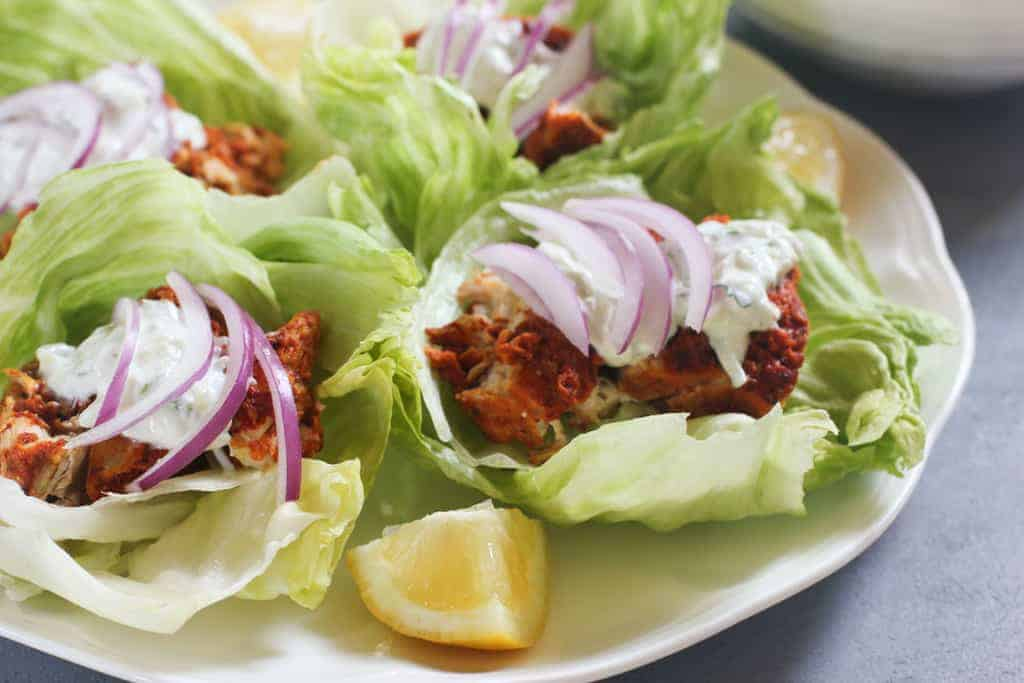 Tandoori Chicken Lettuce Wraps on white platter with lemon wedges