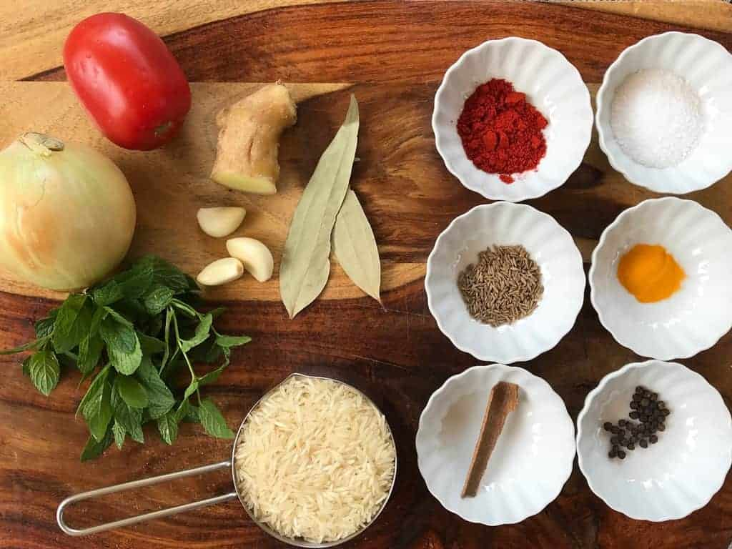 cutting board with bowls of spices and ingredients for Kheema Pulao