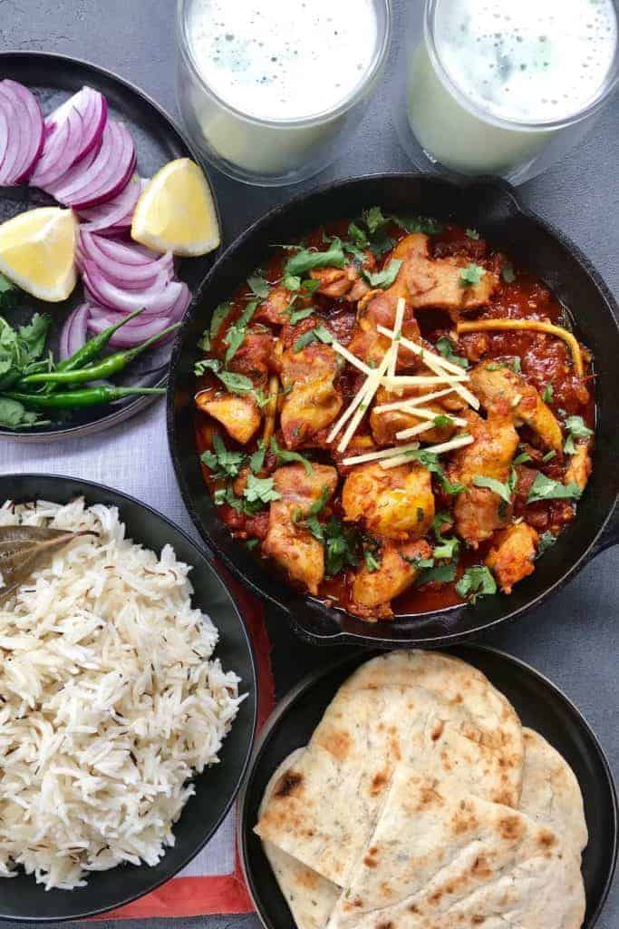 Chicken Karahi in a pan with rice, naan, sliced onions, lemon wedges and green chilies.