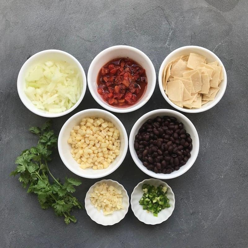 6 white bowls with ingredients for chicken tortilla soup. Diced onions, fire roated tomatoes, tortilla pieces, corn kernels, black beans, garlic and jalapeño. Bunch of cilantro on the side.