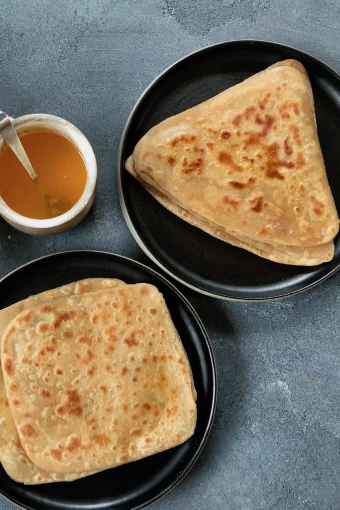 2 square parathas in a platter, 2 triangle parathas in a platter and a silver bowl of ghee