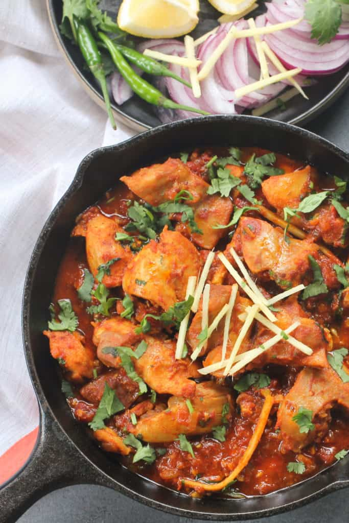 Chicken Karahi garnished with cilantro and ginger in a serving bowl