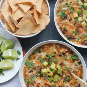 Two bowls with chicken tortilla soup, garnished with cubed avocados, cilantro and cheese. A plate on the left with lime wedges and chopped cilantro. Bowl of homemade baked tortilla chips.