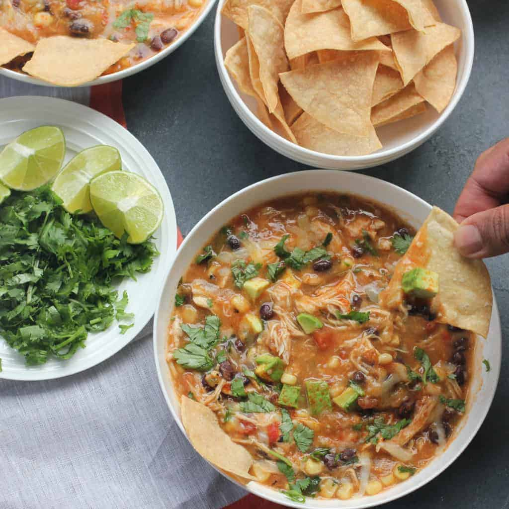 Chicken Tortilla Soup served in a white bowl. Using baked tortilla chips to scoop to soup. Bowl of baked tortilla chips and a plate with lemon wedges and chopped cilantro