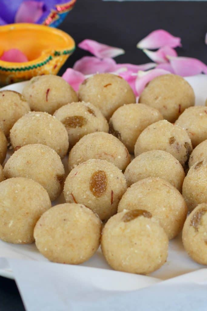 Rava Coconut Ladoo in a white platter with colorful clay lamps on the outside.