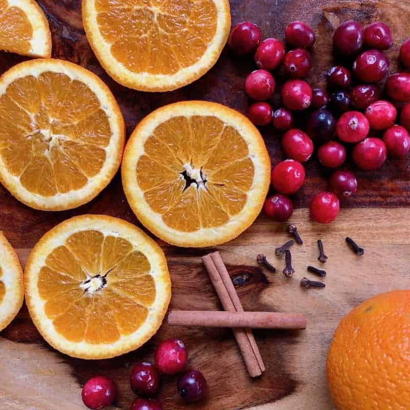 Orange slices, fresh cranberries, cinnamon sticks and cloves on a wooden cutting board