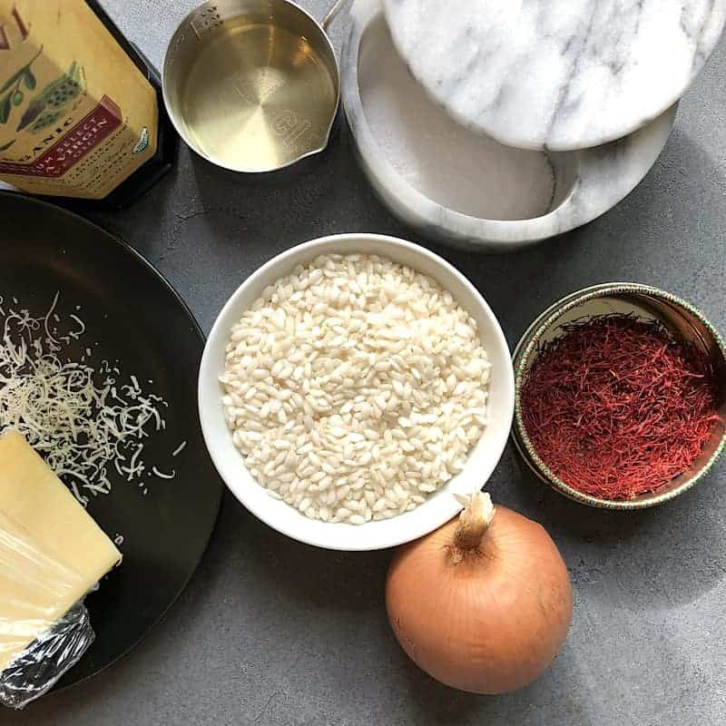 Ingredients for saffron risotto - rice, onion, saffron, wine, salt, oil and parmesan cheese