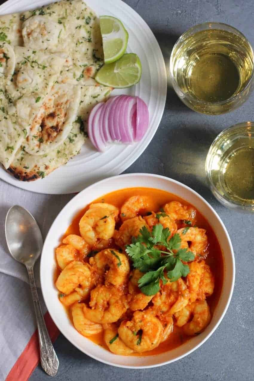 Shrimp curry in a white serving bowl, a white plate with cut up naan, sliced red onions and lemon wedges. Sparking drink in 2 cups on the side.