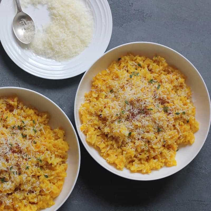 Saffron Risotto, garnished with parmesan cheese and saffron served in 2 white bowls. A plate of grated parmesan cheese on the side with a spoon.