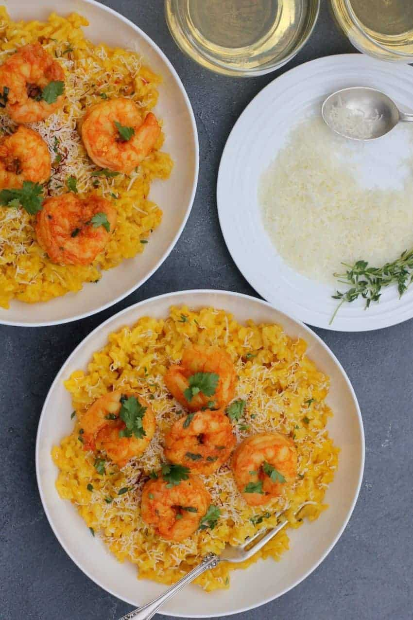 Curried Shrimp served over Saffron Risotto, garnished with choppied cilantro served in 2 white bowls. A plate of grated parmesan cheese on the side, with few srings of thyme and a spoon.