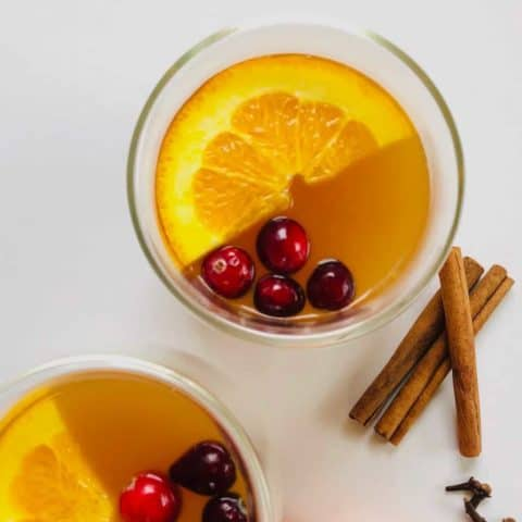 2 cups with spiced apple cider, a wedge of orange and 4 cranberries floating on top. Orange slices, cinnamon sticks and cloves next to the cups on the table.