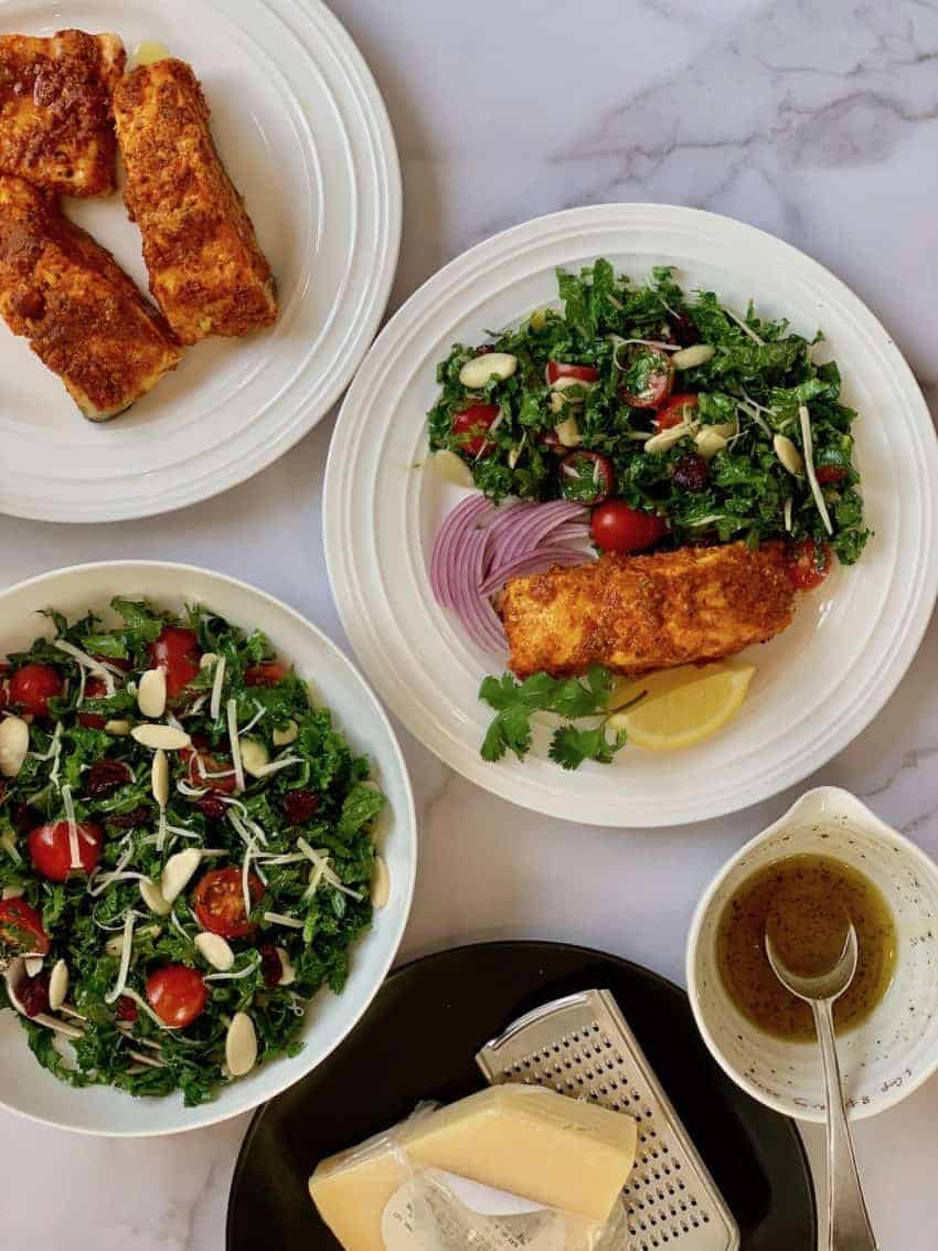 Tandoori Salmon served with kale salad in a white plate. Bowl of salad and a platter with tandoori salmon on the side