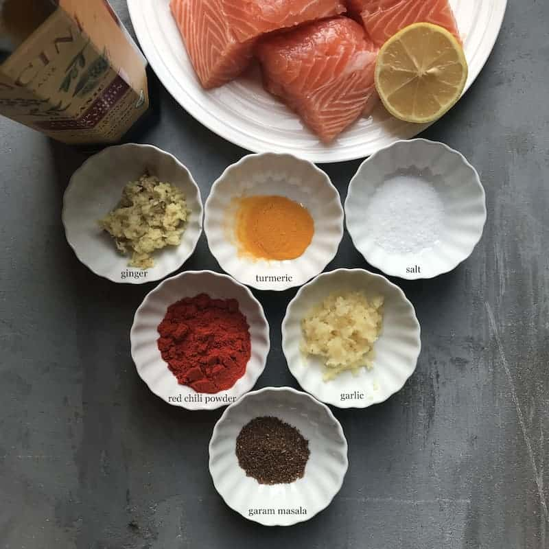 6 small bowls with spices - ginger, turmeric, saltm red chili powder, garlic & garam masala. Bottole of Olive oil and a white plate with salmon fillets and lemon wedge