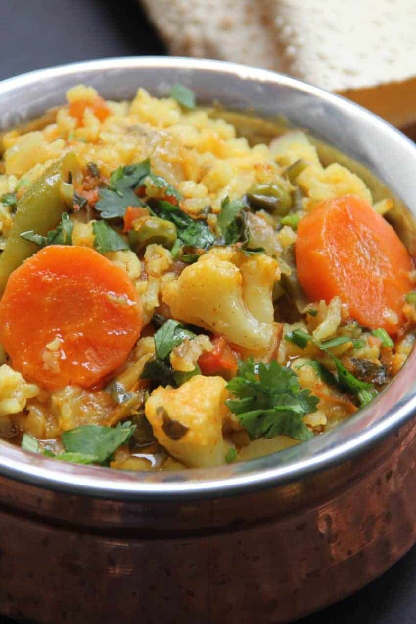 Copper Bowl with vegetable & lentil khichdi , roasted papadums on the side.
