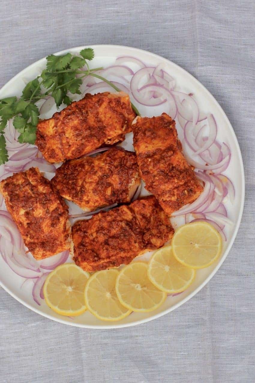 Tandoori Salmon in a white platter with sliced lemons,sliced red onions and cilantro around the fish.