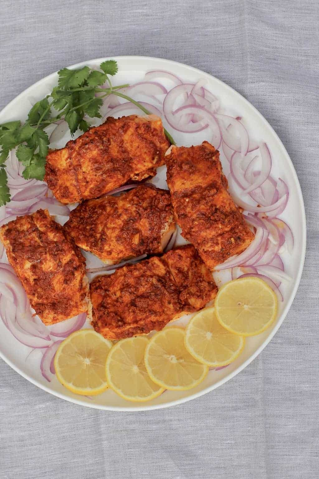 Tandoori Salmon fillets in a white platter surrounded by sliced lemons, sliced onions and cilantro