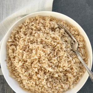 Cooked Brown rice in a white bowl with a fork