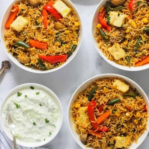paneer and vegetable biryani served in 3 bowls with raita