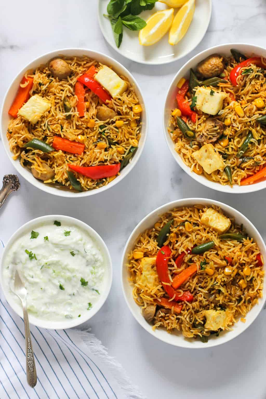 paneer and vegetable biryani served in 3 bowls with raita