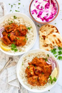 Chicken Tikka Masala served over white rice with naan and raita on the side