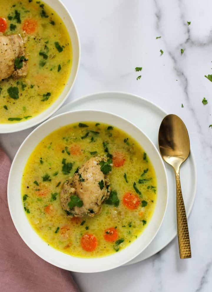 chicken mulligatawny soup served in 2 white bowls garnished with cilantro