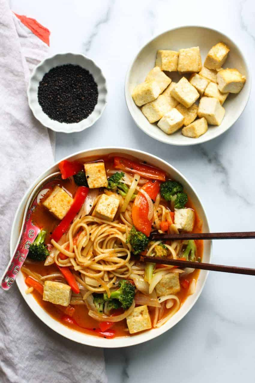 coconut curry noodle soup in a white bowl with chopsticks on one side and a soup soup on the other side immersed in the soup. A small bowl of stir fried tofu and black sesame seeds on the side